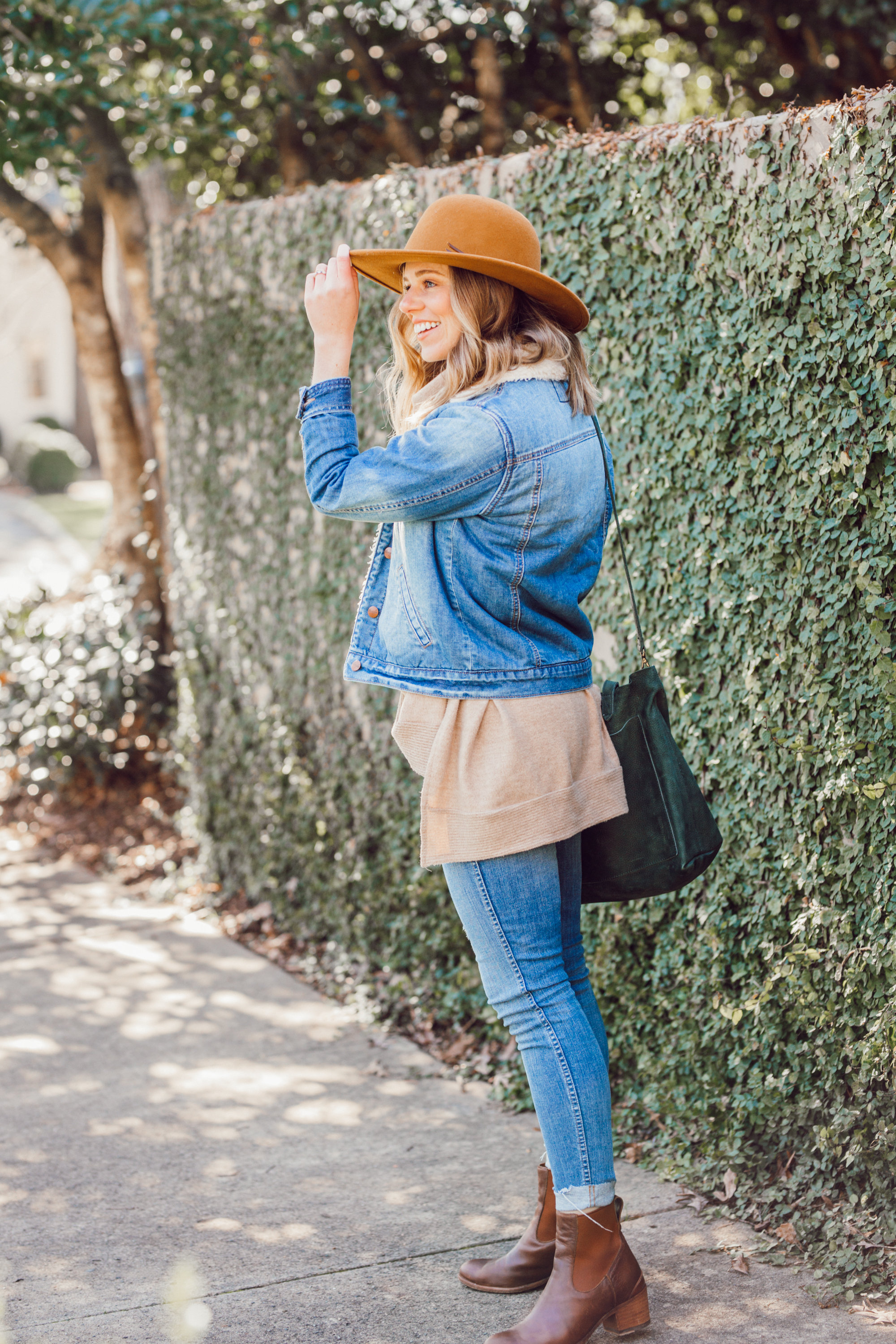 Favorite Winter Boots featured by top US fashion blogger Laura Leigh of Louella Reese; Image of woman sherpa denim jacket, Madewell high-waist skinny jeans, Madewell suede transport tote, Bronze wool hat, Ariat Two24 wilder boots.