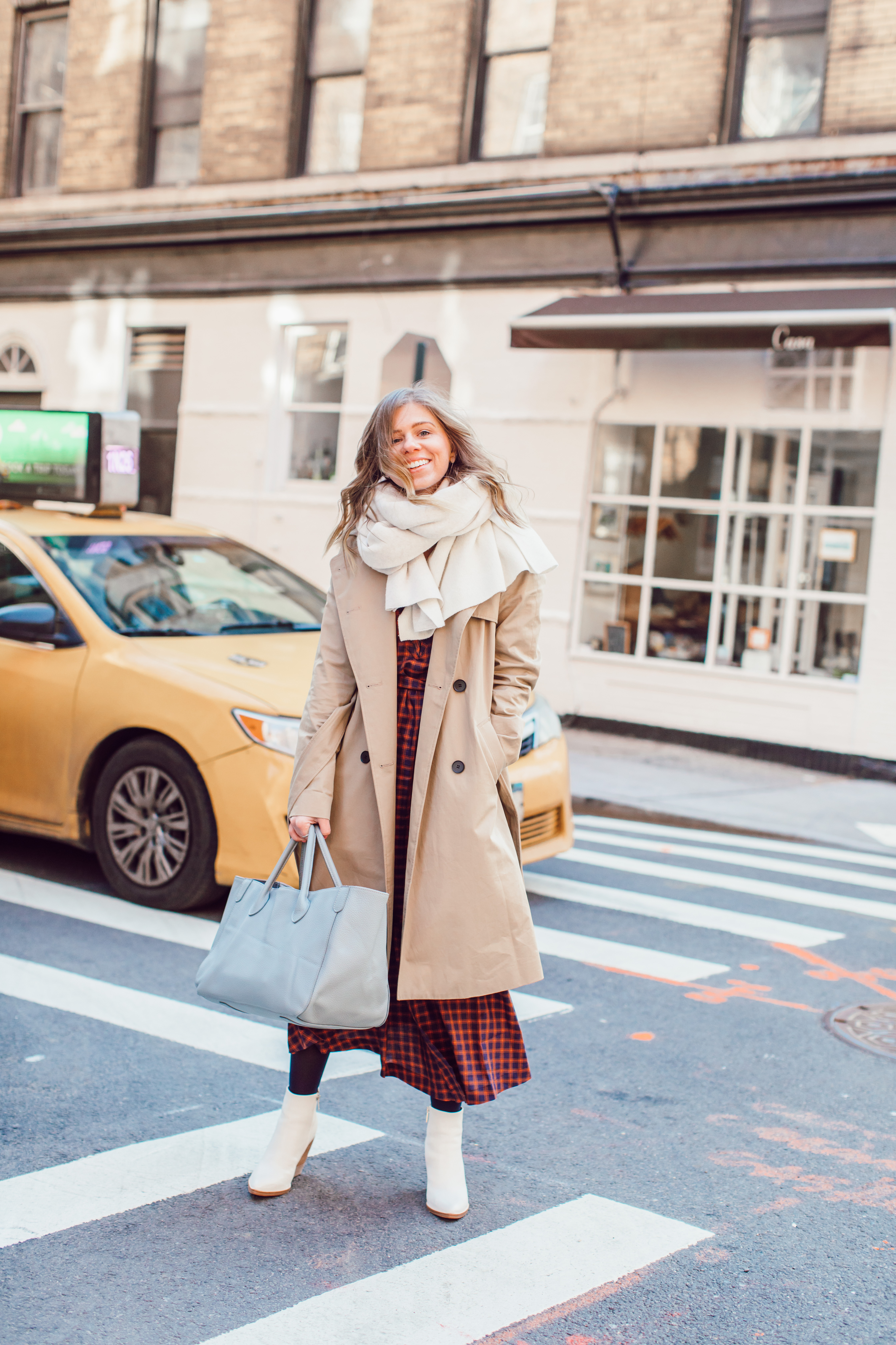 The Perfect Trench Coat styled by top US fashion blogger Laura Leigh of Louella Reese; Image of woman wearing Everyone Drape Trench Coat, & Other Stories Plaid Midi Dress, Marc Fisher LTD Belle Booties, Zac Beck Bags Medium Classic Tote | How to Style a Trench Coat for Winter