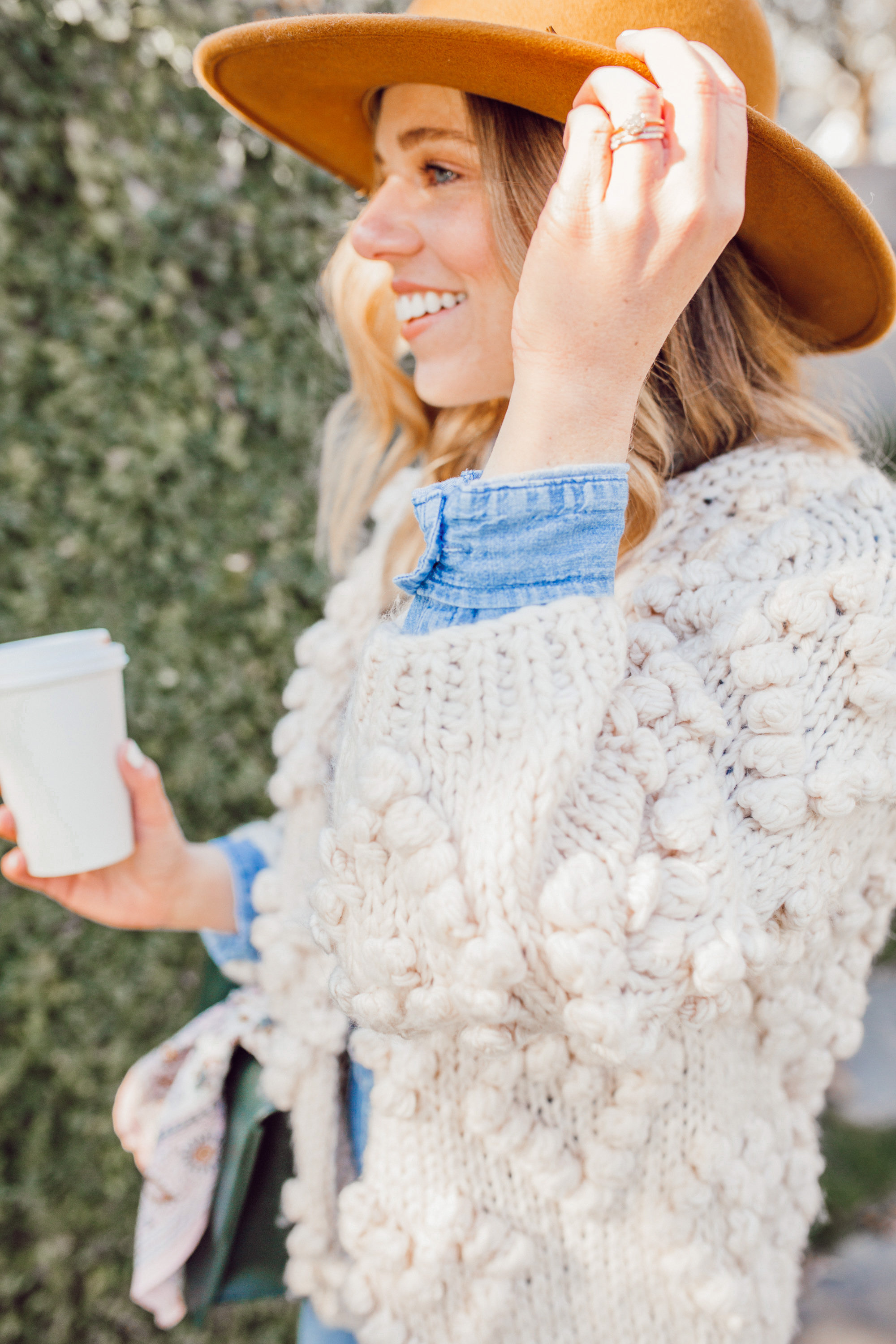 The Importance of Buying Pieces You LOVE - Even If Trendy featured on top US life and style blog Louella Reese| Image of a woman wearing Chicwish Knit Your Love Cardigan, Madewell Overalls, Yellow Wool Hat | Heart Pom Cardigan Sweater